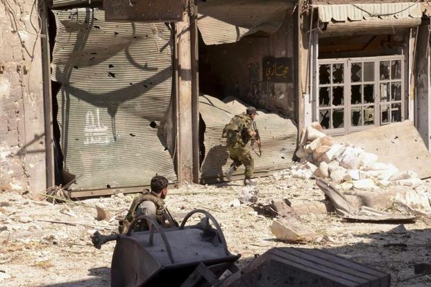 Soldiers loyal to Syrian President Bashar al-Assad take cover in the al-Arqoub neighbourhood in Aleppo city. Photo: Reuters